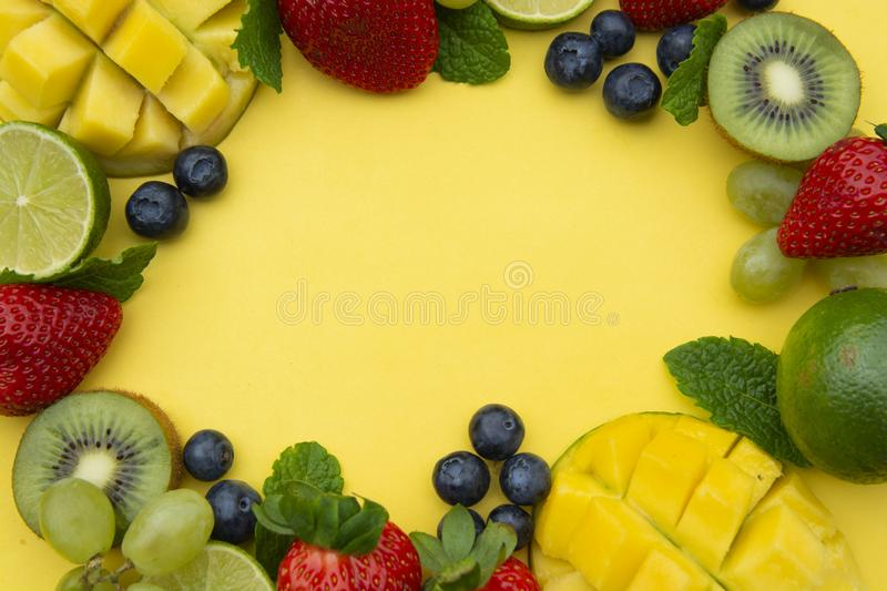 Creative layout made of summer fruits, frame. Tropical flat lay. Grapes, mango, strawberry, blueberry, kiwi, mint, lime, citrus royalty free stock images