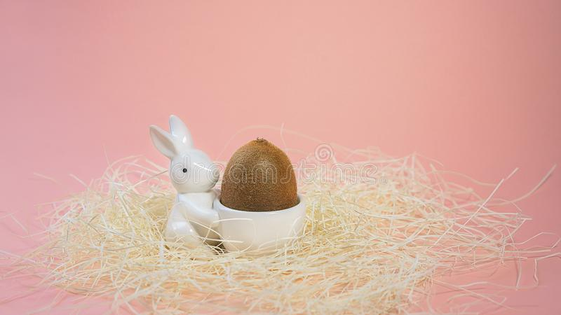 Creative layout made of white ceramic bunny holds a kiwi as easter egg on pink background. Minimal style of concept for gift or royalty free stock photos