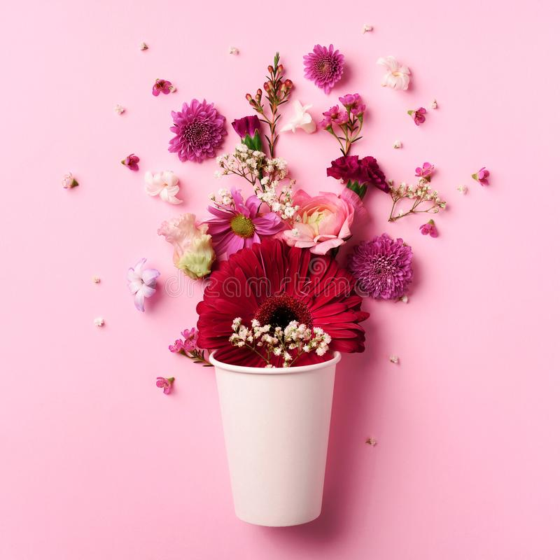 Creative layout made of white paper cup with pink flowers. Flat lay, top view. Square crop. Valentines day, Woman day concept. stock image