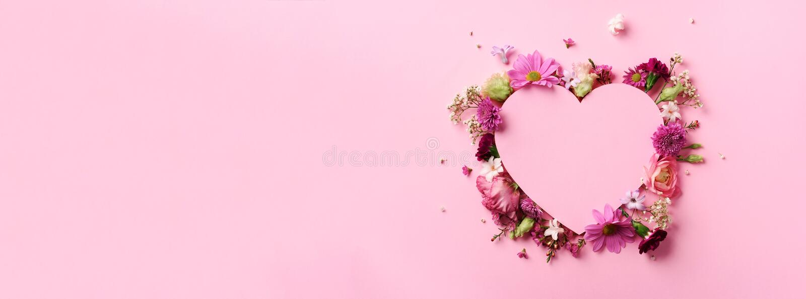 Creative layout with pink flowers, paper heart over punchy pastel background. Top view, flat lay. Spring, summer or garden concept. Present for Woman day stock image