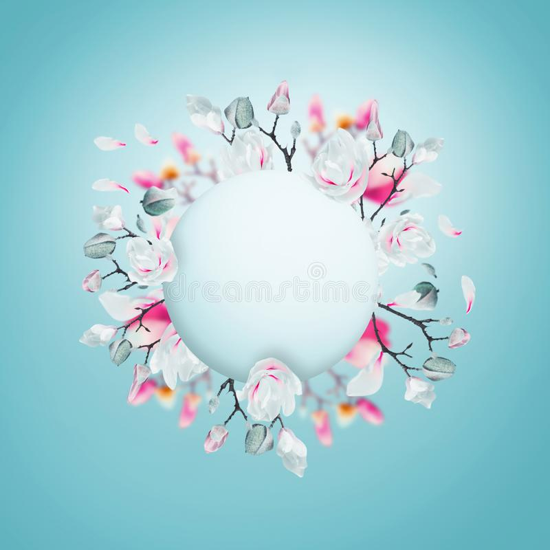 Creative layout with pink and white spring blossom branches made in shape of circle frame at light blue background. Magnolia stock photo