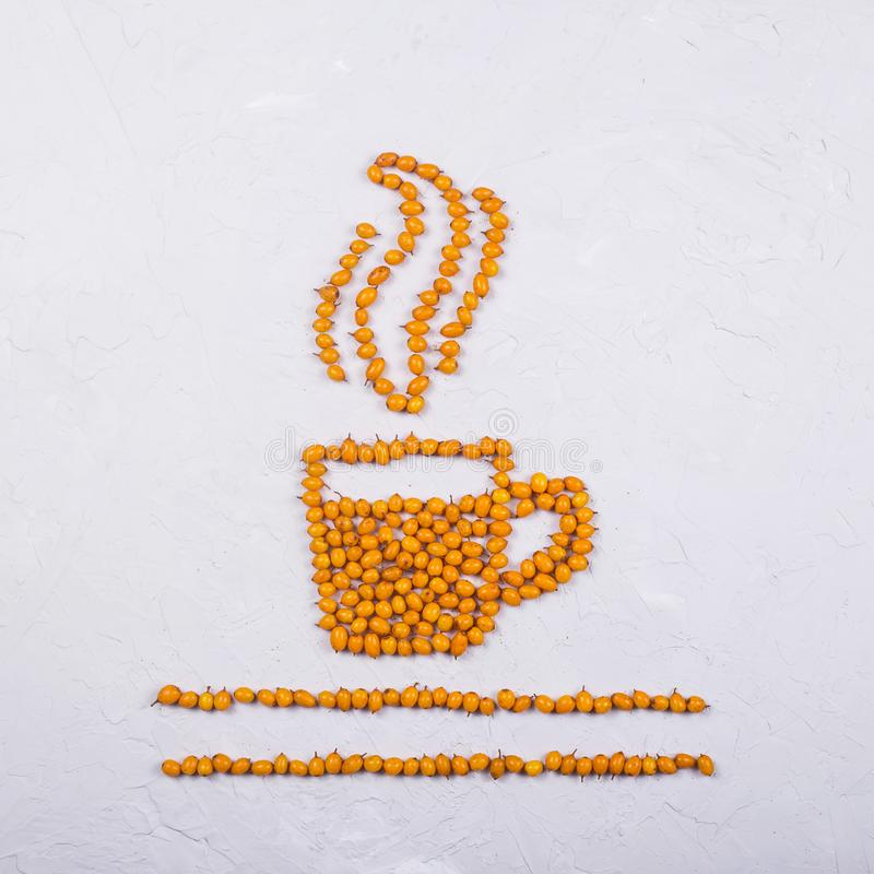 Creative layout of sea buckthorn berries on a neutral gray background. A layout of bright orange sea buckthorn berries in the shape of a cup of tea with steam royalty free stock photography
