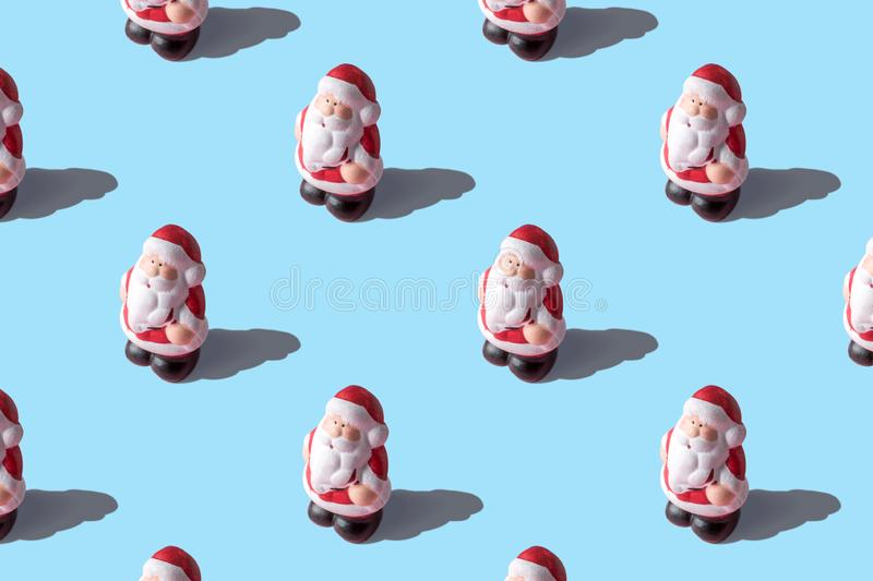 Creative layout of small Santa Clauses on bright background. Minimal Christmas or New Year concept royalty free stock photo