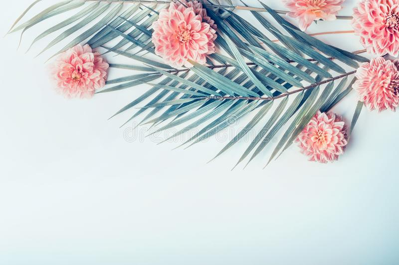 Creative layout with tropical palm leaves and pastel pink flowers on light turquoise blue desktop background, top view, place for stock image