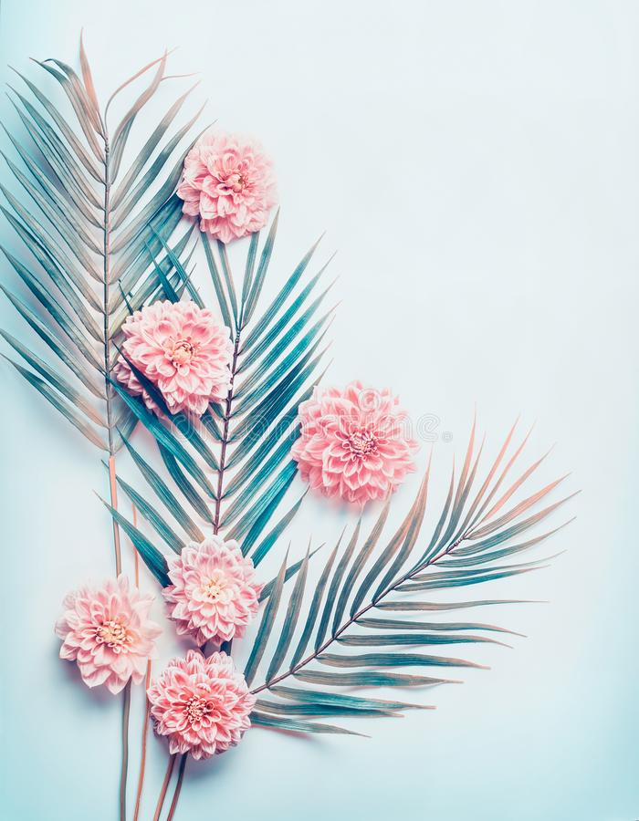 Creative layout with tropical palm leaves and pastel pink flowers on turquoise blue desktop background, top view, place for text. Vertical royalty free stock image