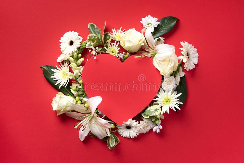 Creative layout with white flowers, paper heart over red background. Top view, flat lay. Spring and summer concept. stock photos