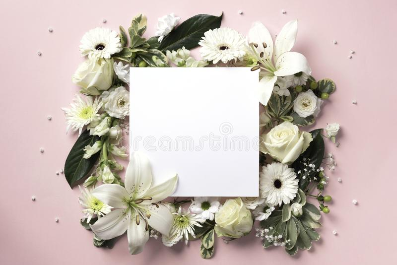 Creative layout with white flowers, square shape paper for copyspace over pink background. Top view, flat lay. Spring stock image