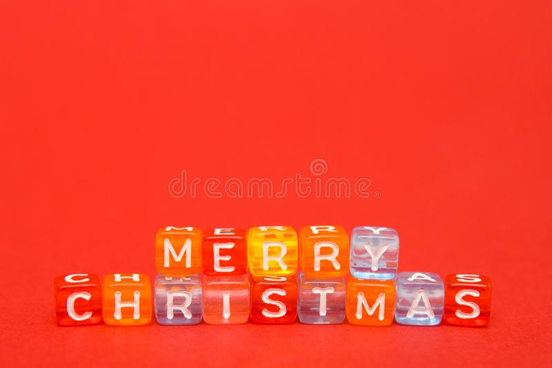 Creative layout words merry christmas made of colorful blocks on red background. free space for note and text. Flat lay. New Year royalty free stock image