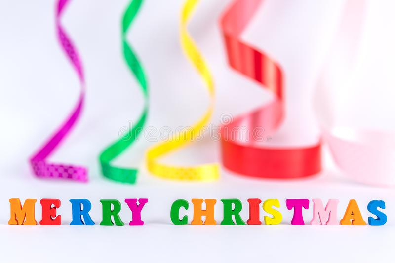 Creative layout of words merry christmas made of wooden multi-colored letters on white background with blurred curly satin ribbons royalty free stock photos