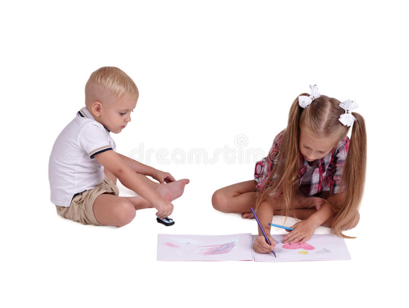 Kids drawing isolated on a white background. Preschool boy and girl with color pencils. Creativity concept. Copy space. stock images