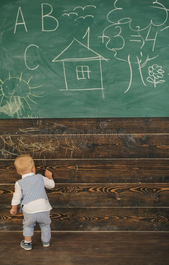 Creative little boy painting doodle on wall in classroom. Creative artist in school stock photo