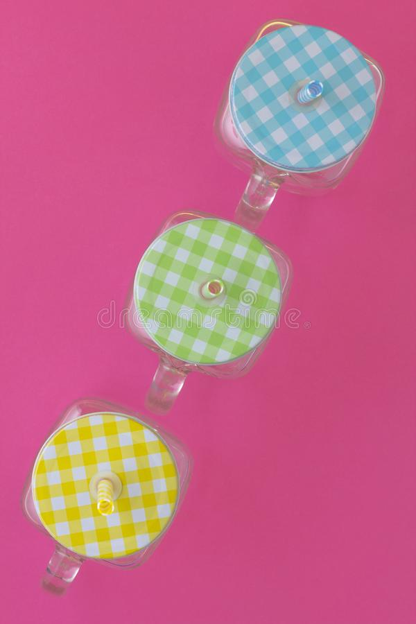 Creative look at the colored jars for a summer cold drink on a p. Ink background. Top view royalty free stock images