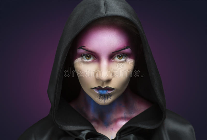 Creative look. Woman with purple blue face art and big black hood. Mystery girl creative idea to Halloween party. Beauty close up portrait, perfect facial skin stock images