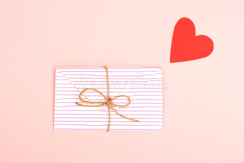 Envelope on pink background. Creative love or Valentine day background made with cute envelope, heart shape paper and rope. Love letter or message concept stock image