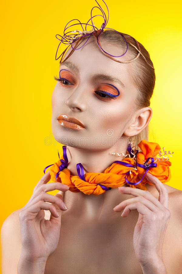 Creative make-up and hairstyle. Portrait of young girl On the bright orange background royalty free stock photos