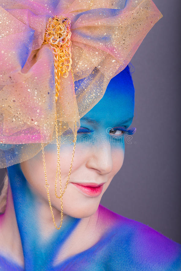 Creative makeup. Airbrush. Blue, indigo, violet makeup. Seasoned professional creative eye make-up, hair. Golden headdress on the girl royalty free stock photos