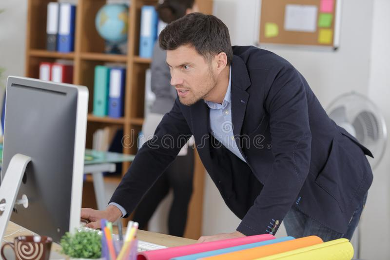 Creative male office worker with computer. Male royalty free stock photos
