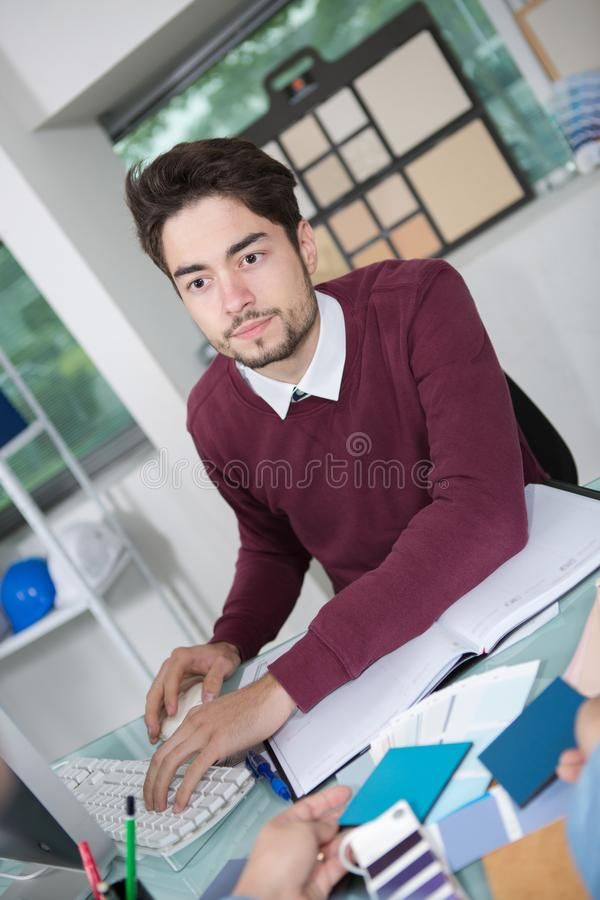 Creative male office worker with computer talking to client. Young stock photography