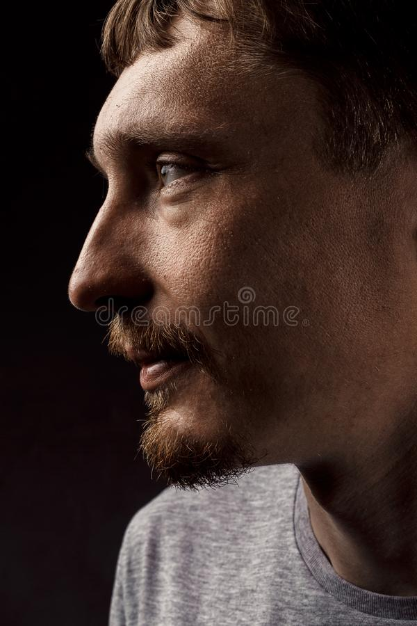 Creative male portrait. Handsome young man looking to the side, profile view stock photography