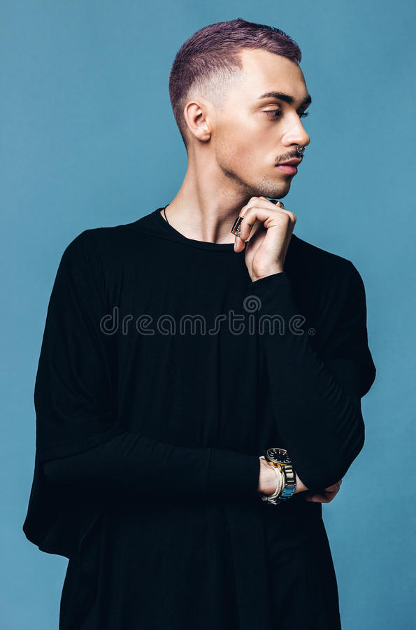Creative man with purple hair on blue background royalty free stock images
