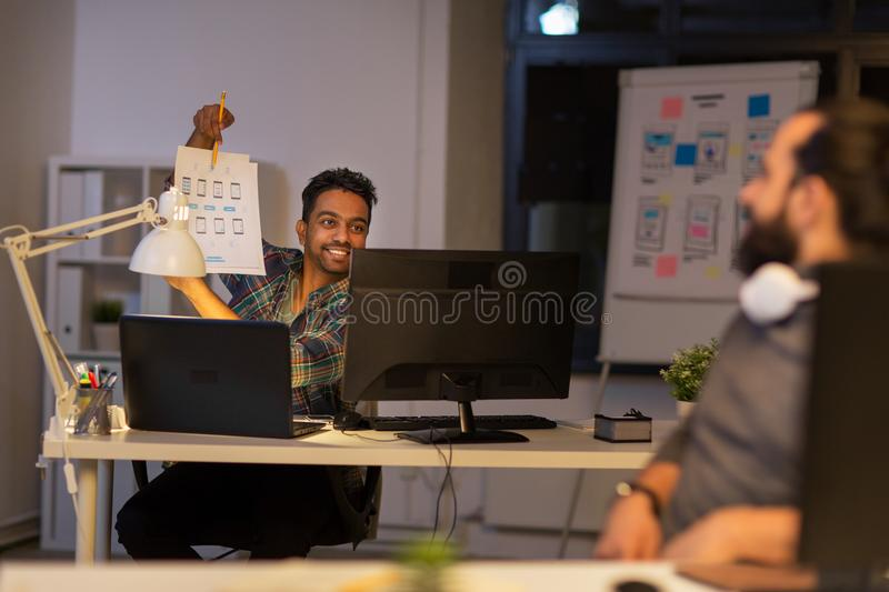 Creative man showing papers to colleague at office royalty free stock photos