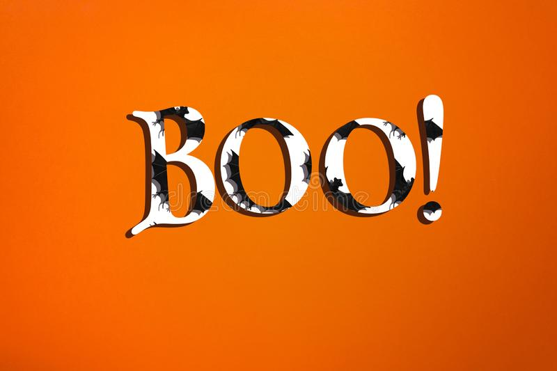 Creative minimalistic halloween text on orange background. White letters with bats and shadows stock photos