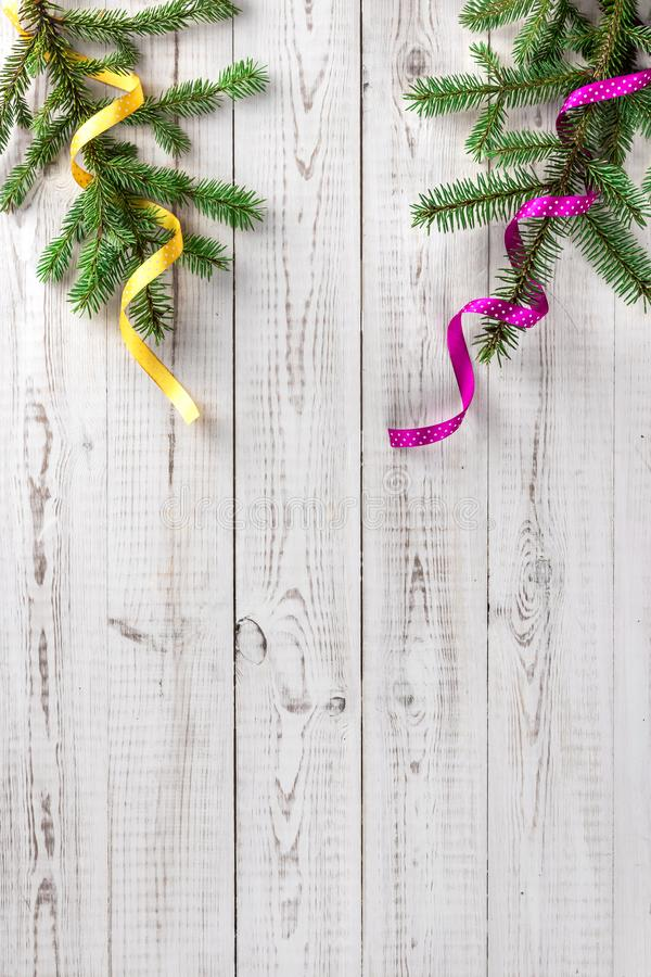 Creative minimalistic winter composition with two spruce branches and yellow and pink curly ribbon on white wooden background. royalty free stock photo