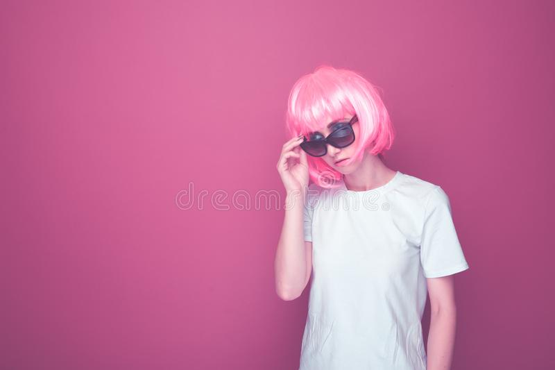 Creative model in a 90s style in a pink studio. Creative model in a 90s style in a pink studio stock photos