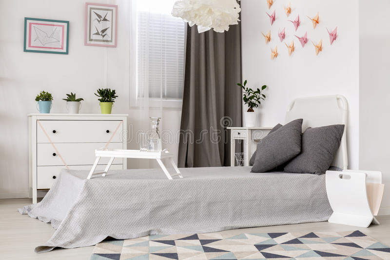 Creative origami wall decor idea. Light bedroom with simple white furniture and origami wall decor royalty free stock photography
