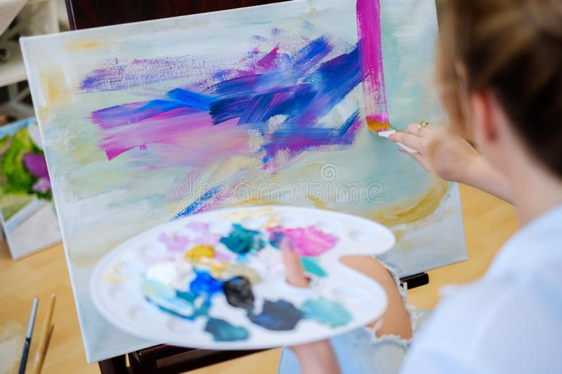 Creative painter paints a colorful picture in her studio.  stock images