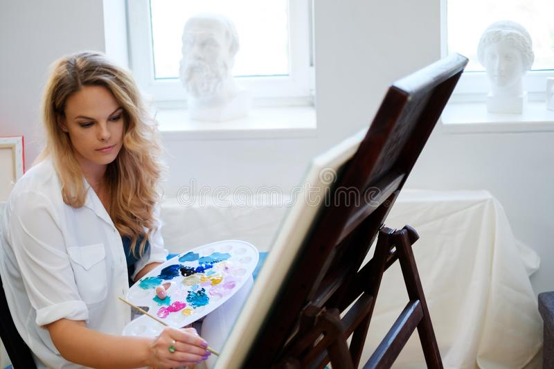 Creative painter paints a colorful picture in her studio.  royalty free stock photography