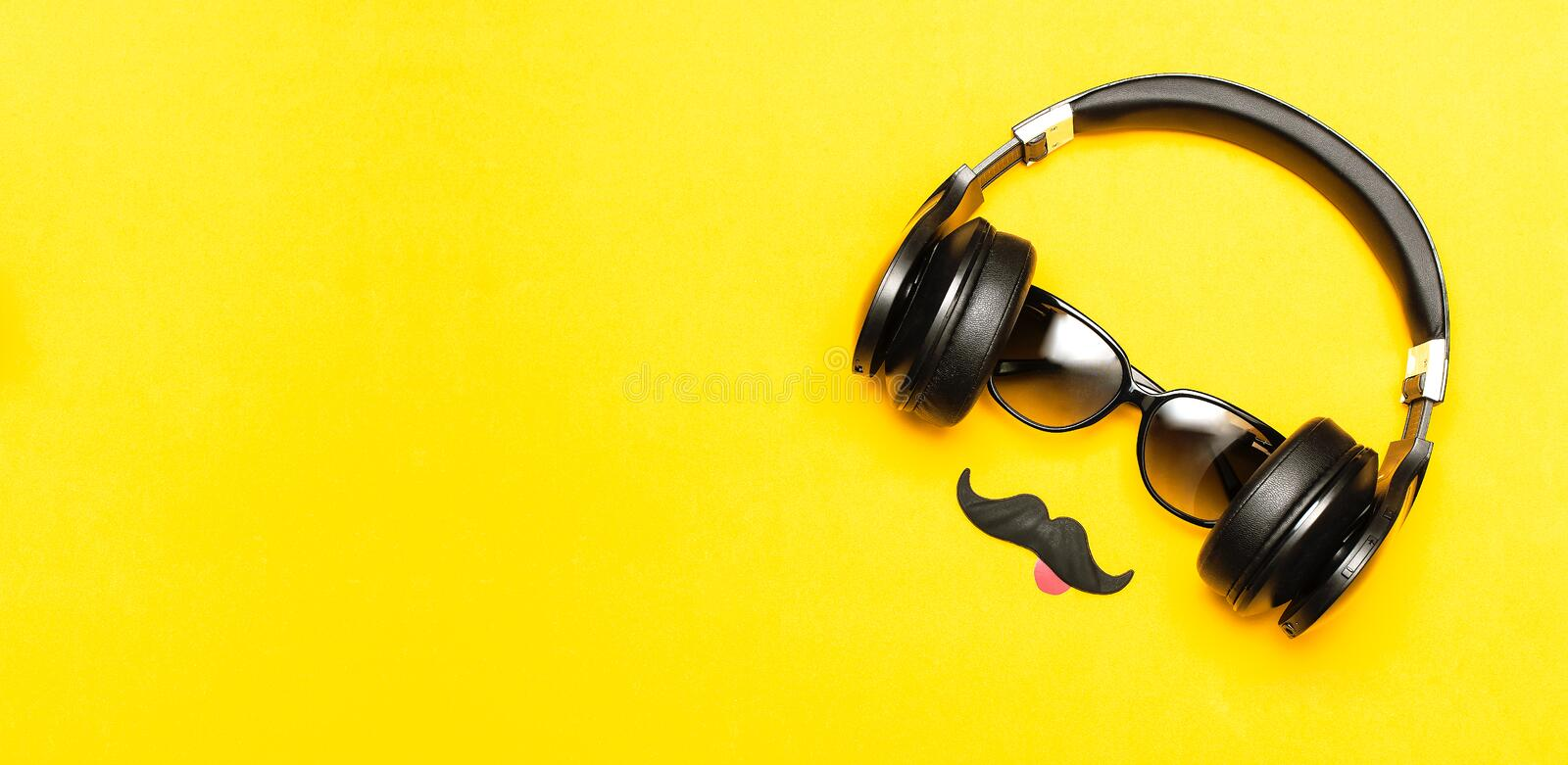Creative party decoration concept. Black mustache, Sunglasses, headphones for music, props for photo booths carnival parties on stock image