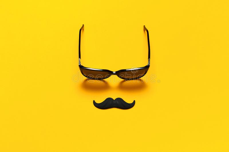 Creative party decoration concept. Black mustache, sunglasses, props for photo booths, carnival parties on yellow background top royalty free stock photo