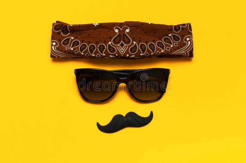 Creative party decoration concept. Black mustache, sunglasses, props for photo booths, carnival parties on yellow background top stock images