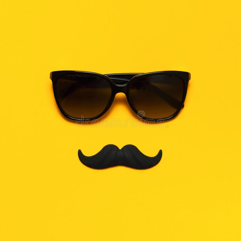 Creative party decoration concept. Black mustache, sunglasses, props for photo booths, carnival parties on yellow background top royalty free stock image