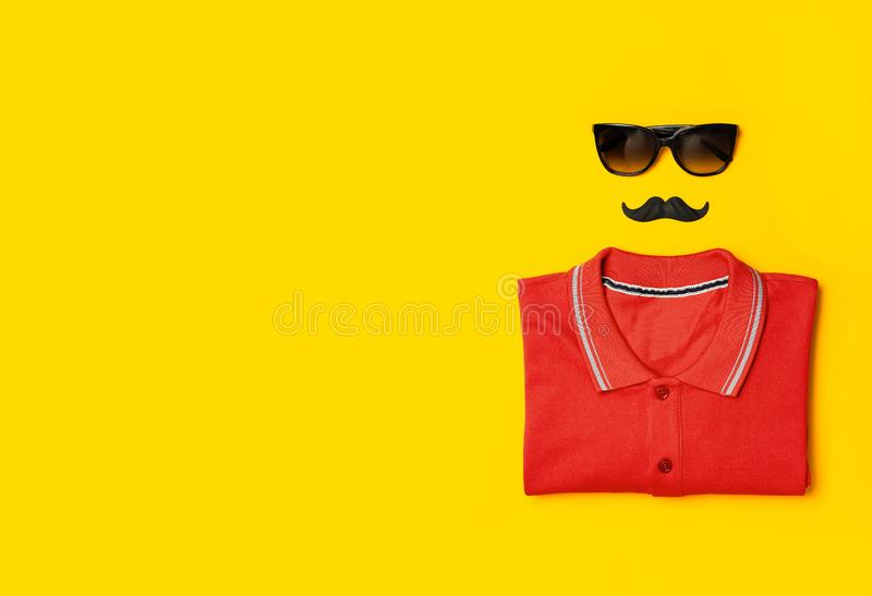 Creative party decoration concept. Black mustache Sunglasses red polo shirt props for photo booths carnival parties on yellow. Background top view flat lay copy stock image