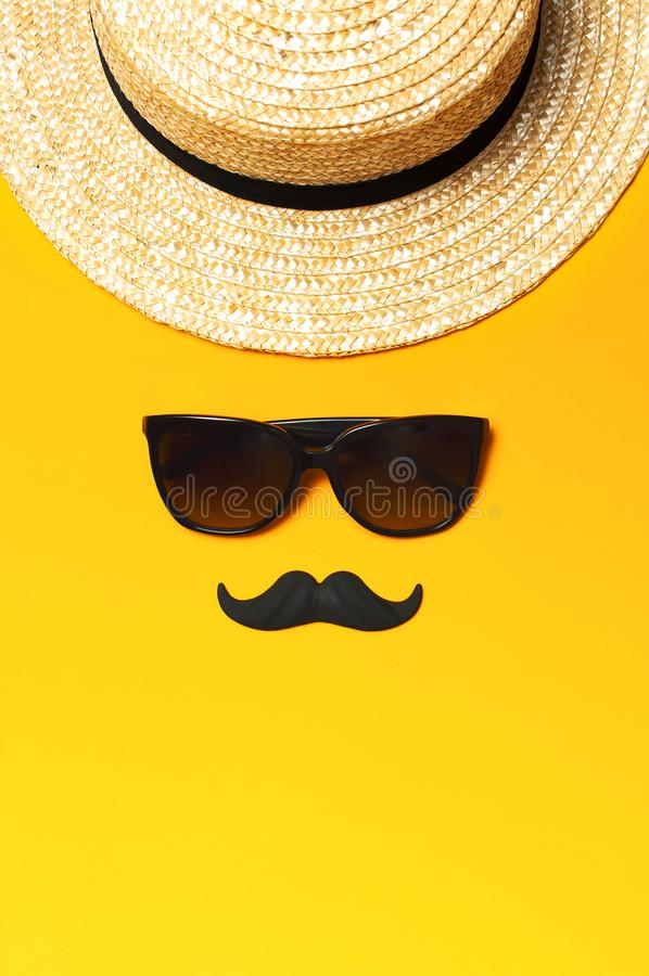 Creative party decoration concept. Black mustache, sunglasses, straw hat, carnival parties on yellow background top view flat lay royalty free stock photos