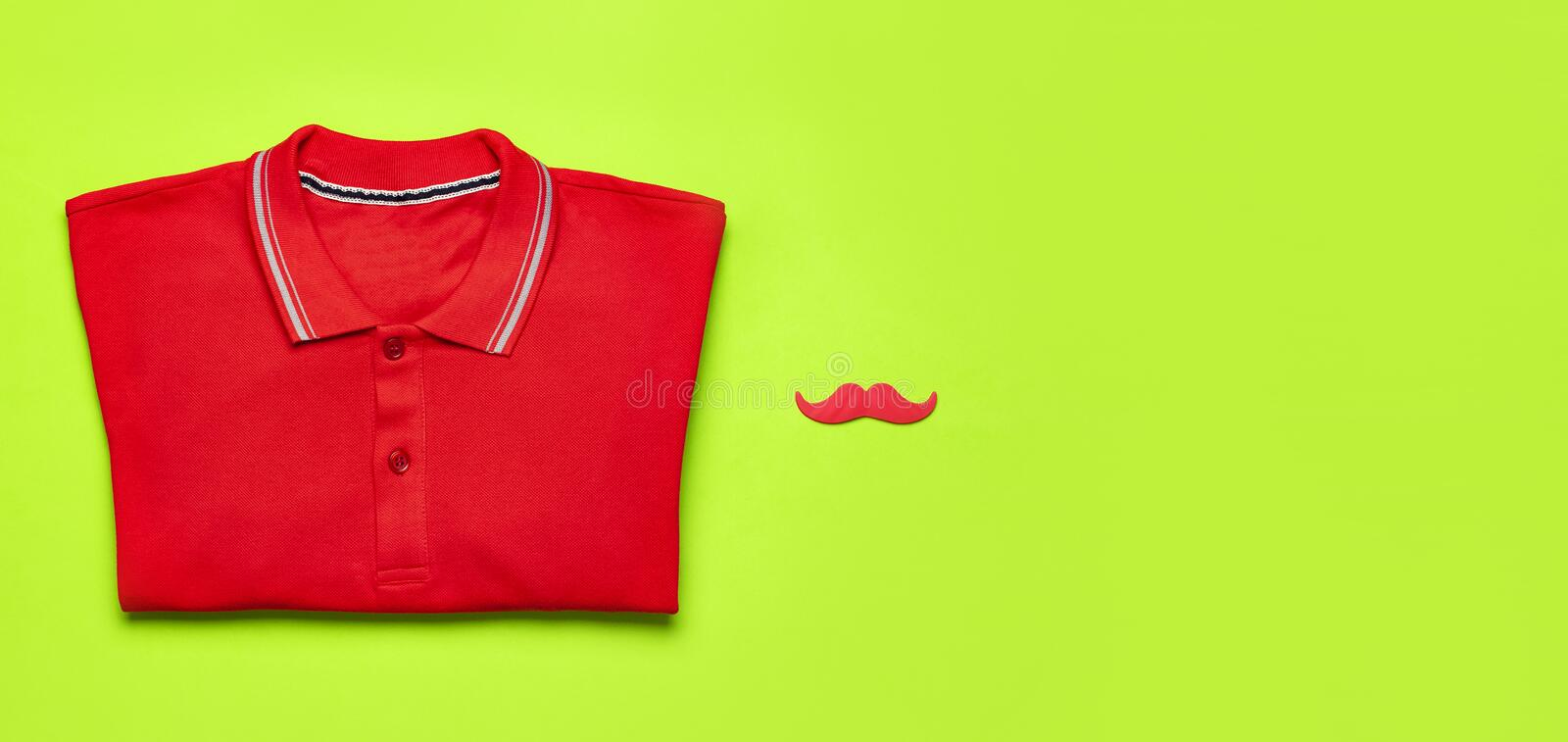 Creative party decoration concept. Red mustache, red polo shirt, props for photo booths, carnival parties on green background top. View flat lay copy space stock images