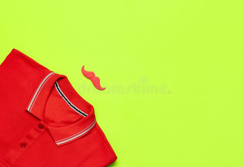 Creative party decoration concept. Red mustache, red polo shirt, props for photo booths, carnival parties on green background top. View flat lay copy space stock photo