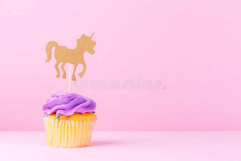 Creative pastel fantasy holiday card with cupcake, confetti and. Unicorn. Baby shower, birthday, celebration concept. Horizontal stock photo