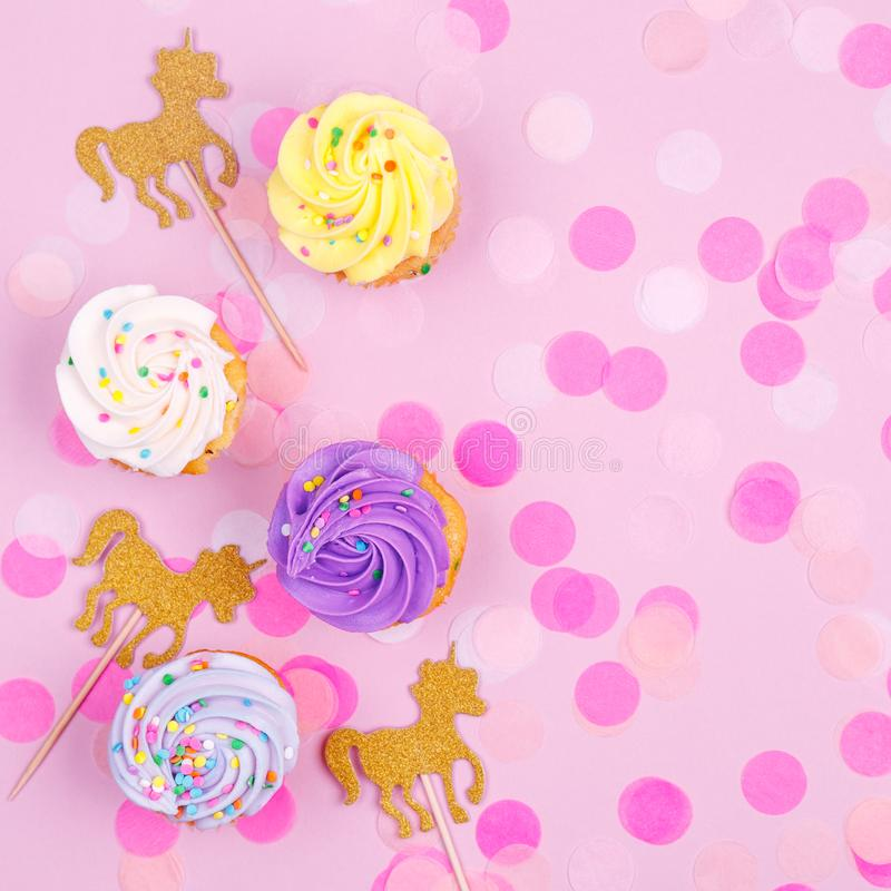 Creative pastel fantasy holiday card with cupcake, confetti and. Unicorn. Baby shower, birthday, celebration concept. Square stock photos