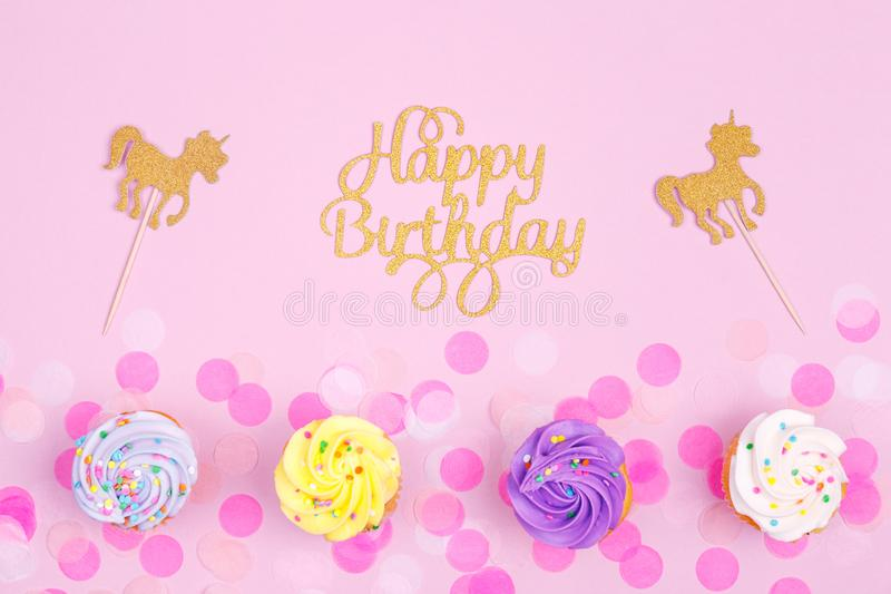 Creative pastel fantasy holiday card with cupcake, happy birthday lettering and unicorn. Baby shower, birthday, celebration. Concept. Horizontal stock photography