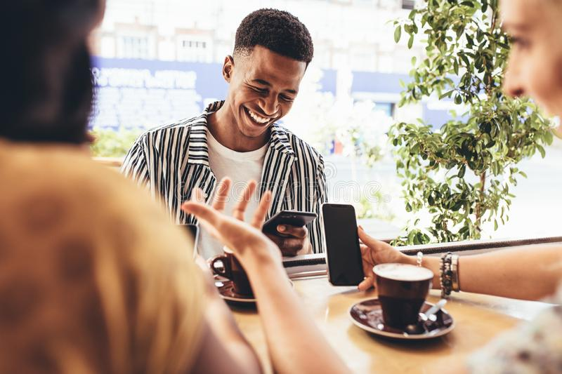 Creative people meet up at cafe. Group of creative people meeting up in at cafe. Smiling young friends sitting at coffee shop using smart phones royalty free stock photography