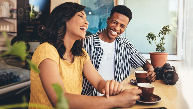 Creative people meet up at cafe. Male and female friends talking and smiling at cafe. Creative people meet up at cafe, having a great time together stock photos