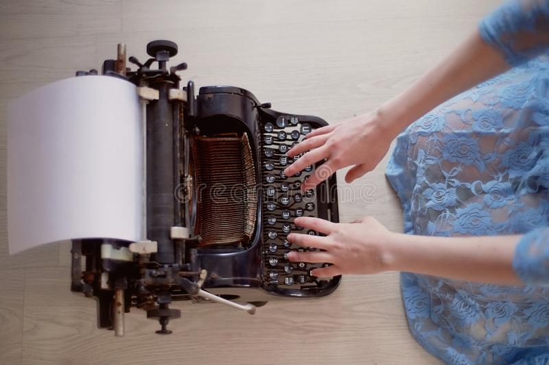 A creative person, author of books, writer of bestsellers,a journalist typing on an old typewriter. Inspiration in the. A creative person, author of books royalty free stock image