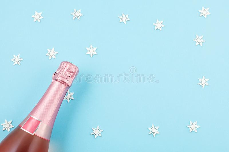 Creative photo of champagne bottle with confetti on blue backgro. Und. Flat lay of christmas, anniversary, new year celebration concept royalty free stock photography