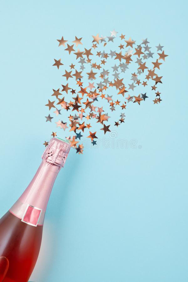 Creative photo of champagne bottle with confetti on blue backgro. Und. Flat lay of christmas, anniversary, new year celebration concept stock image