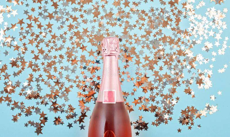 Creative photo of champagne bottle with confetti on blue background. Flat lay of christmas, anniversary, new year celebration. Concept stock photography