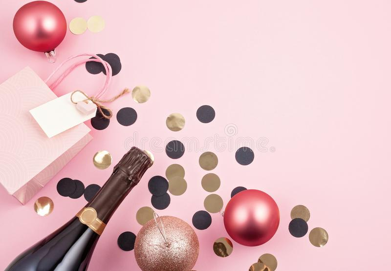 Creative photo of champagne bottle with confetti. Flat lay of ch. Creative photo of champagne bottle with confetti and christmas decoration on pink background royalty free stock photos