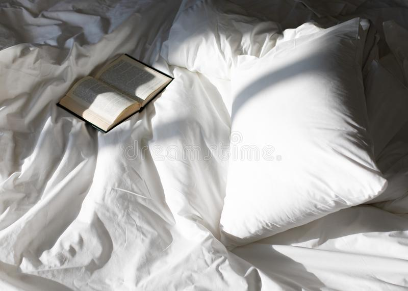Creative photo composition with book and white bed under the sun light from window stock image